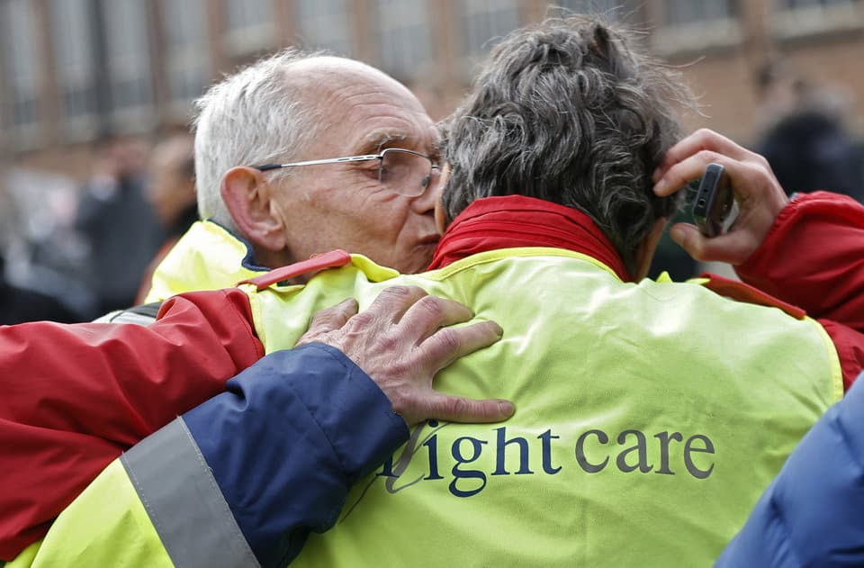 Airport workers embrace as they leave the scene of explosions at Zaventem airport near Brussels, Belgium, March 22, 2016. REUTERS/Francois Lenoir - RTSBLZL